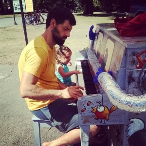 A father and daughter try out a public park piano in Seattle, WA
